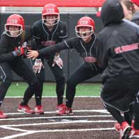 CSB softball players celebrating at home plate